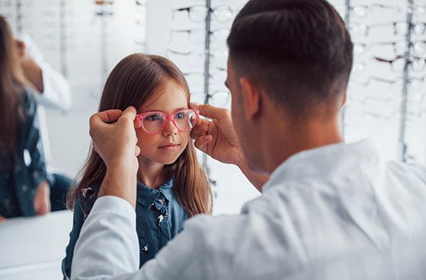 child trying on eyeglasses