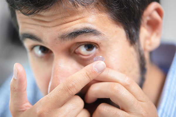 man inserting contacts lens